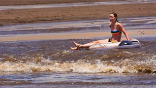 Girl floating on Medano Creek wave