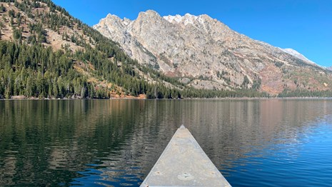 The front of a canoe on a lake.