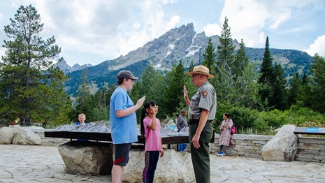 A ranger stands with two kids with a mountain in the background.