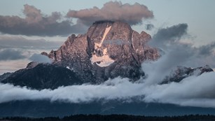 Mount Moran at sunrise with clouds. Skillet Glacier and the Black Dike are prominent.