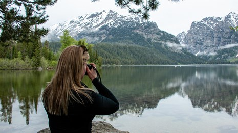 A women takes a photo at a lakeshore.