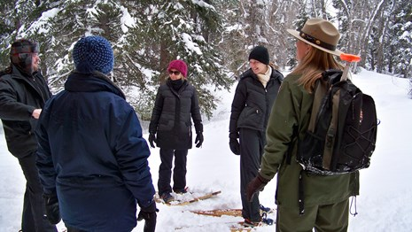 Ranger and park visitors on snowshoes.