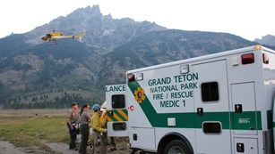 Ambulance and helicopter in front of Mount Teewinot.
