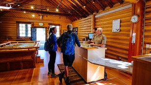 Visitors talk to rangers in a log cabin.
