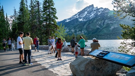 Visitors enjoying an overlook at South Jenny Lake with Mount Teewinot in the background