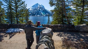 Two visitors enjoy the view of a lake from at an overlook
