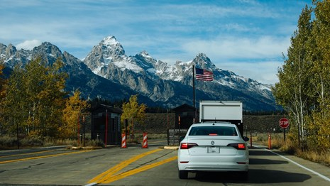 A car drives past a small booth with mountains in the distance.