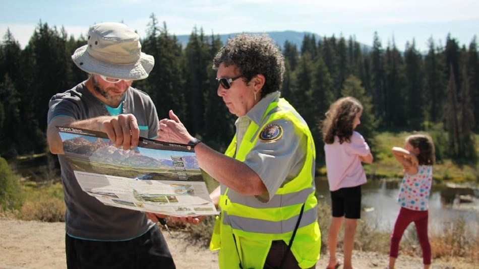 A volunteer gives directions to a visitor in Grand Teton National Park