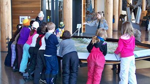 A park ranger teaches a group of students about Grand Teton using a large raised relief map