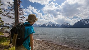 A young hiker looks across a large lake to view the Tetons on the other side