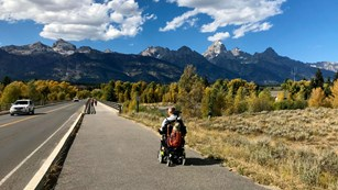 A visitor in a wheelchair on a paved path with mountains in the background.