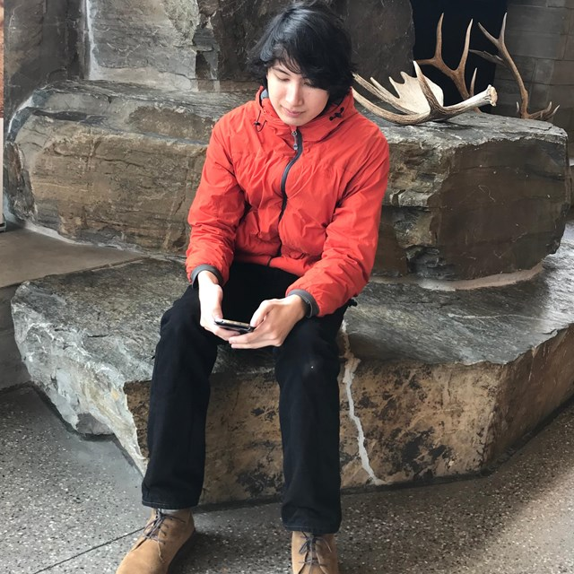 visitor texting at the craig thomas discovery and visitor center