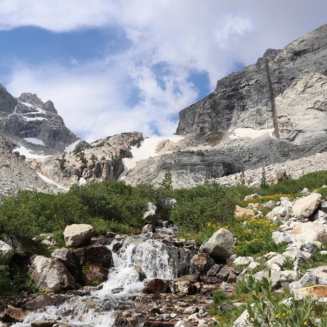 A creek flows through a canyon surrounded by granite mountain peaks