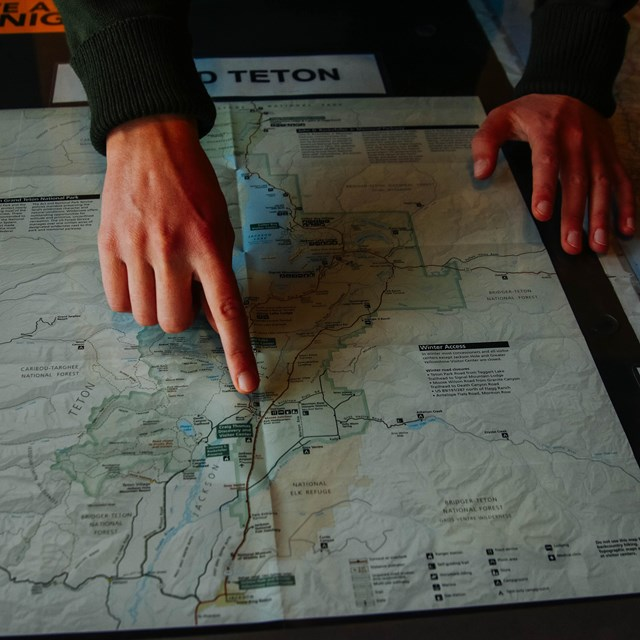 Hands point to a map of Grand Teton.