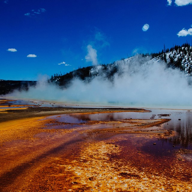 Steam rises off a brightly colored pool.