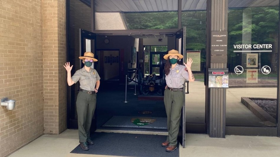 Two Park Rangers waving and opening the Visitor Center doors