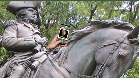 General Greene monument holding an iphone, sitting on horse, forest in foreground