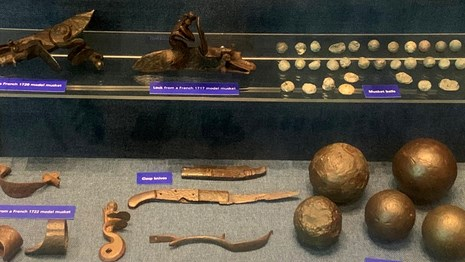 Museum exhibit of musket & cannon balls, & gun pieces blue background