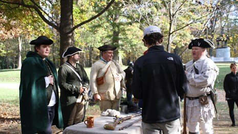 Four living history volunteers in colonial garb talk to a visitor with back turned to camera