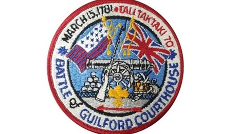A Boy Scout patch featuring guns, cannon balls, American Revolution flags and Boy Scout text