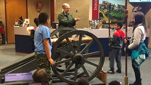 Park ranger teaches three students how to load a 3-pounder cannon and other students look at them.