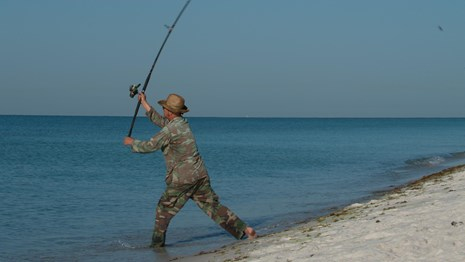 A man casts a fishing line on the edge of a sandy beach.