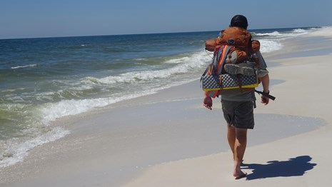 A backpacker walks along the beach near the water line.
