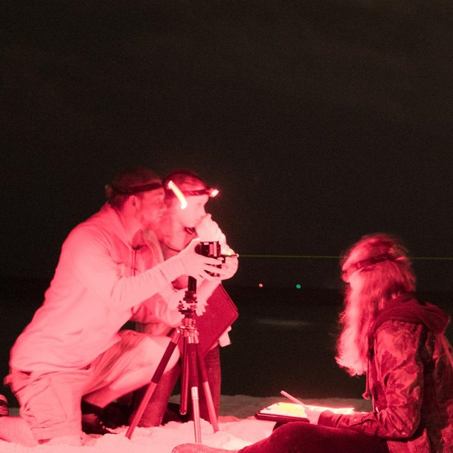 Three people take light measurements of the sky at night.