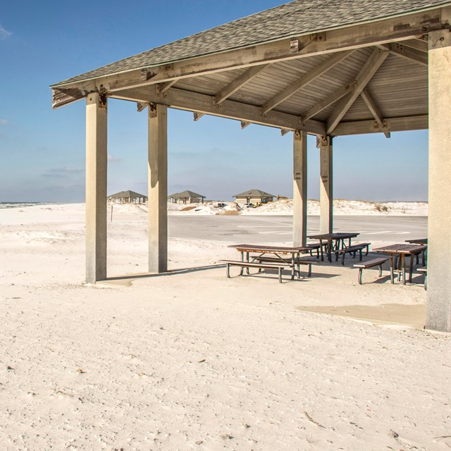 A shade pavilion stands on the edge of a sandy beach.