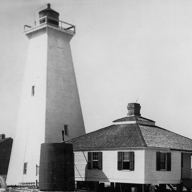 Black and white photo of the second Ship Island Lighthouse and one story keepers quarters.