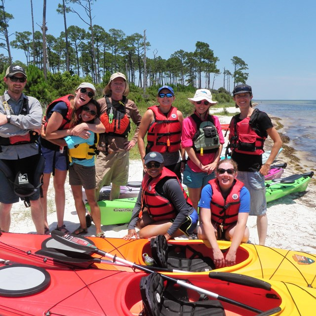 A group of young adults in life-jackets gather around kayaks.