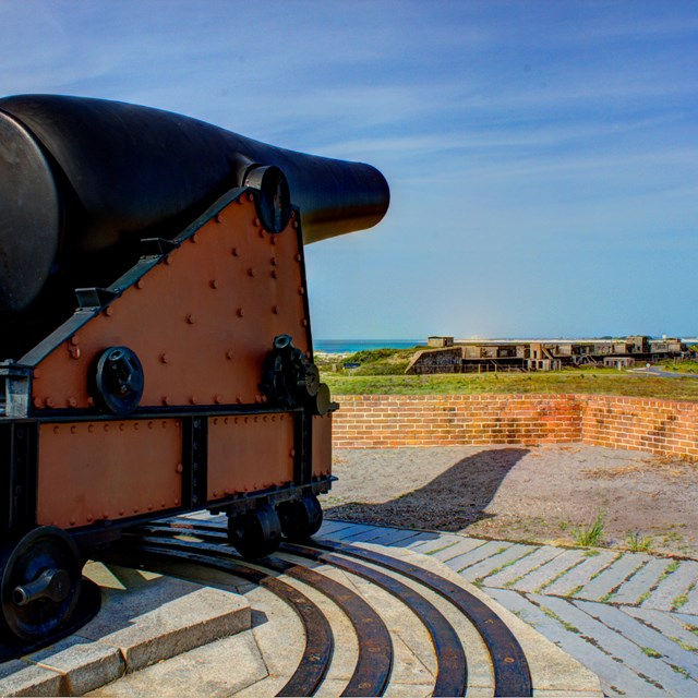 Large cannon sits atop a historic fort.