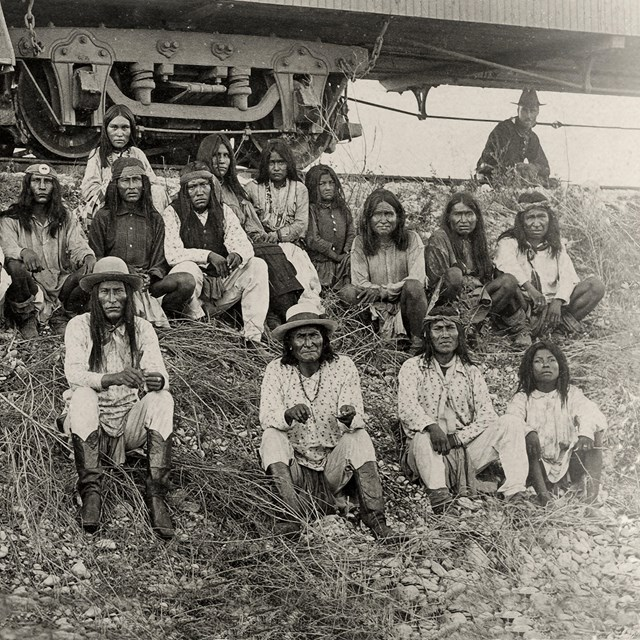 Black and white photo of several American Indians sitting on a hill beside a rail car.