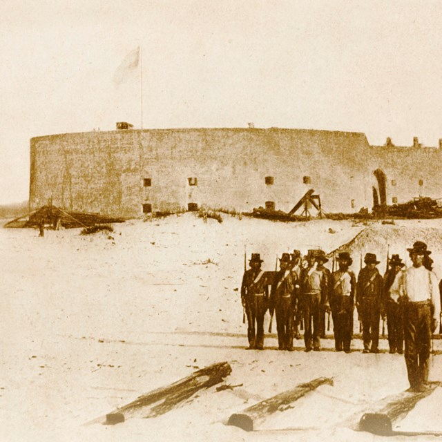 Historic image of soldiers standing in the foreground with a large masonry fort in the background.