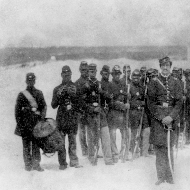 Black and white photo of African American soldiers formed on a beach.