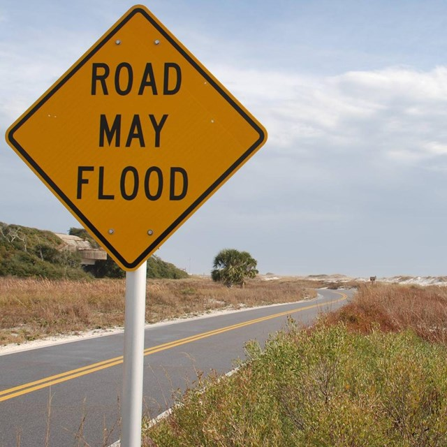 A sign reading road may flood stands next to a road along a beach.