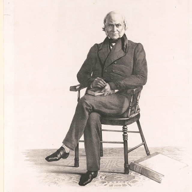 Black and white image of an elderly John Quincy Adams sitting in a wooden chair facing the camera.