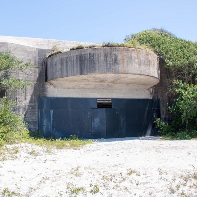 A massive concrete structure surrounded by vegetation sits on a beach.
