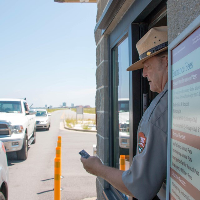 A ranger examines a park pass from an entrance gate window.