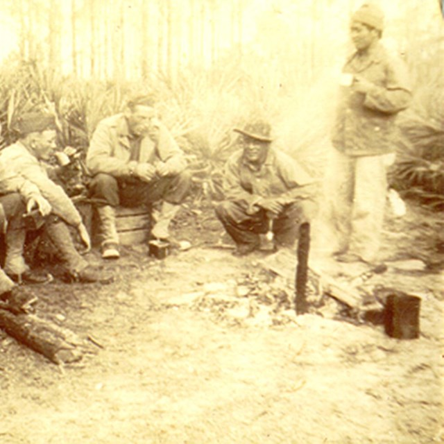 A group of soliders sit in a wooded area in a semi-circle.