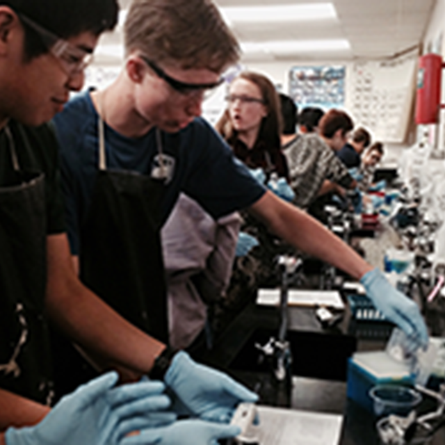 Students in lab gear work with scientific equipment.