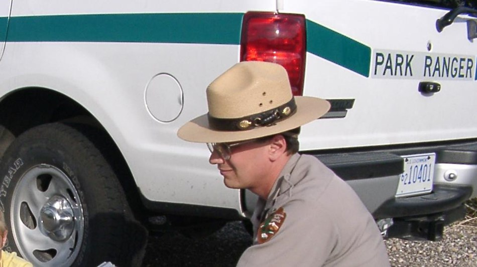 A park ranger kneels next to a patrol vehicle