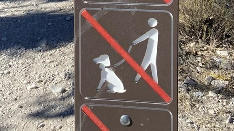 Brown sign denoting that pets are not allowed on trails