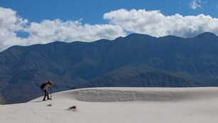 A visitor takes photographs in the gypsum dunes