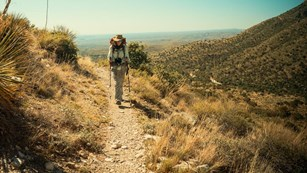 A hiker on a trail leading out of the desert into the mountains