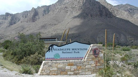 A park entrance sign in front of the visitor center and the mountains