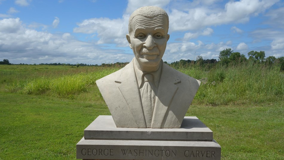 A cast concrete bust of George Washington Carver, depicted as an older man wearing a suit and tie.