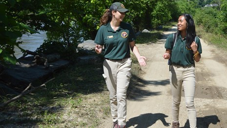 two young ladies who are interns walk along the towpath near Harpers Ferry
