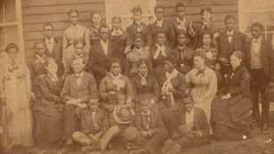 sepia tone image from the 1870s showing a group of African American students and their teachers