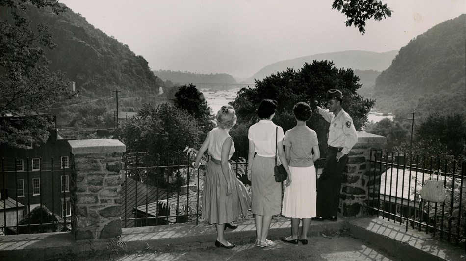 black and white photo of a ranger pointing out the water gap to three women
